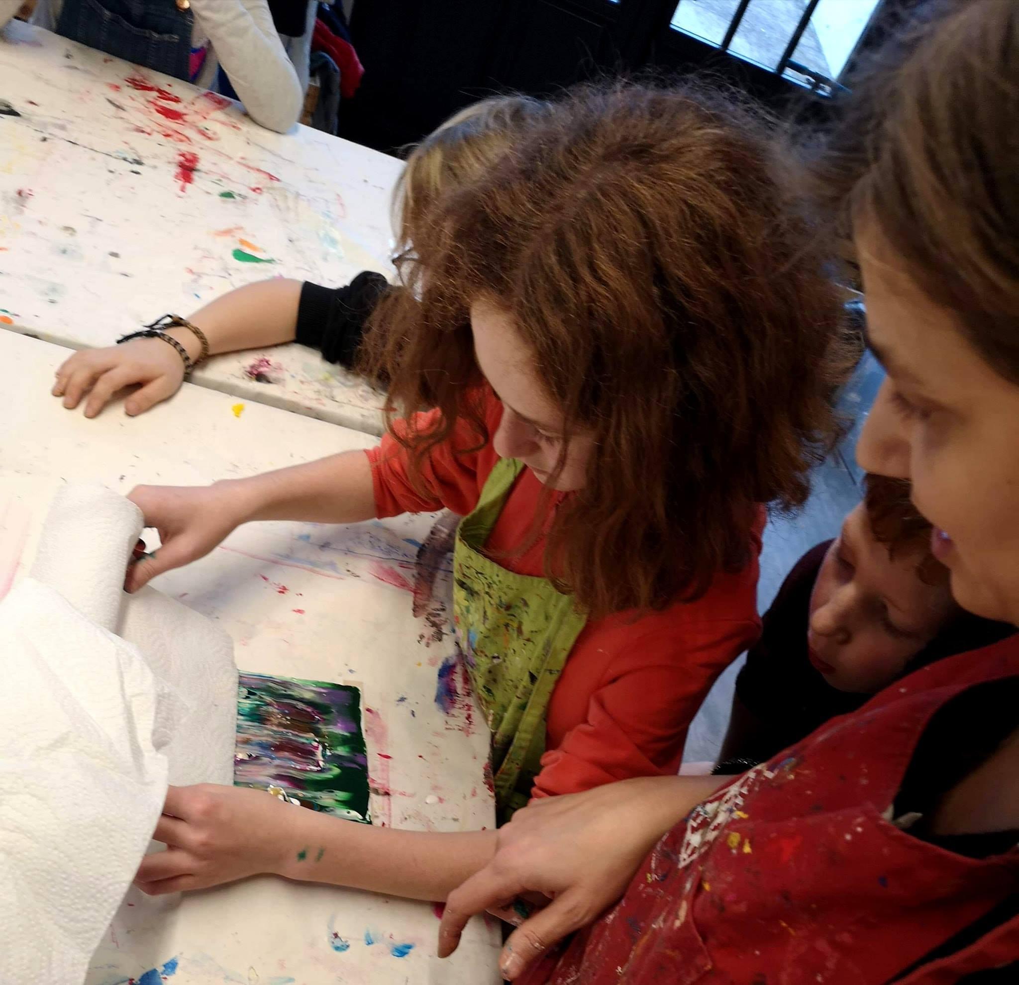 Une encadrante aide une enfant sur la création d'une oeuvre