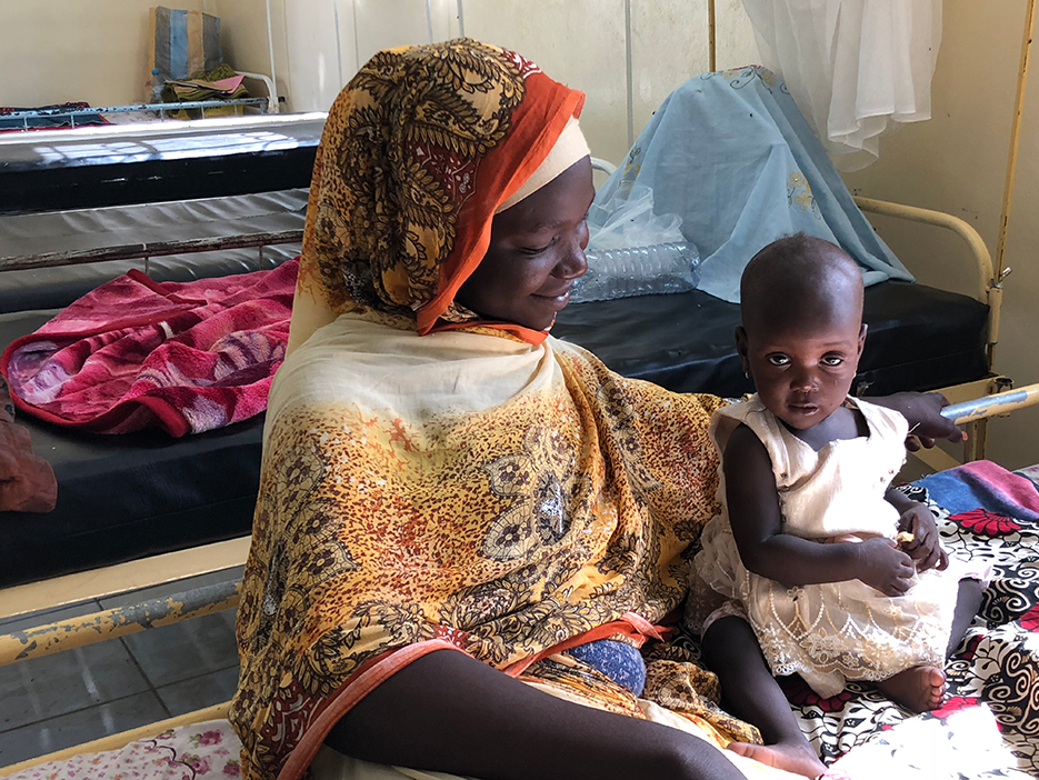 Une mère souriante aux côtés de sa fillette, installées sur un lit d'hôpital.